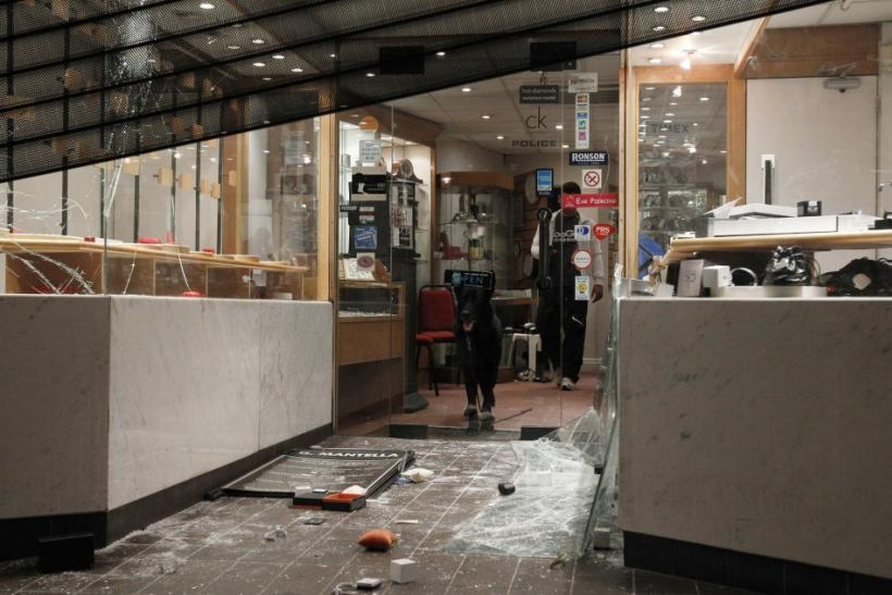 Shards of broken glass lay on the ground outside a damaged jewellery shop in Enfield