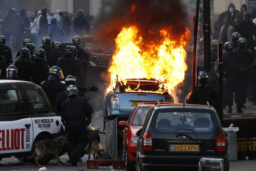 Police officers in riot gear block a road near a burning car on a street in Hackney, east London August 8, 2011