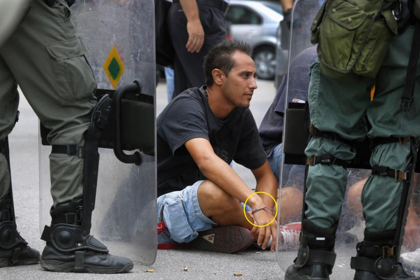 A demonstrator is detained during a protest at the Ministry of Defense on October 4.