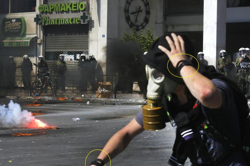 A black bloc protester tosses a tear gas canister back at police during violent clashes following anti-austerity protests on September 26.