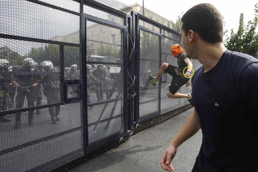 A protester kicks a metal barricade during demonstrations in Athens on October 9.