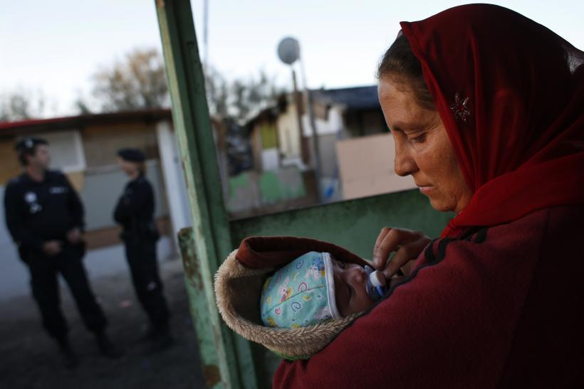 Angela holds her one-month-old son Raul as police officers block the way while an excavator demolishes a neighbor's shack in Madrid's