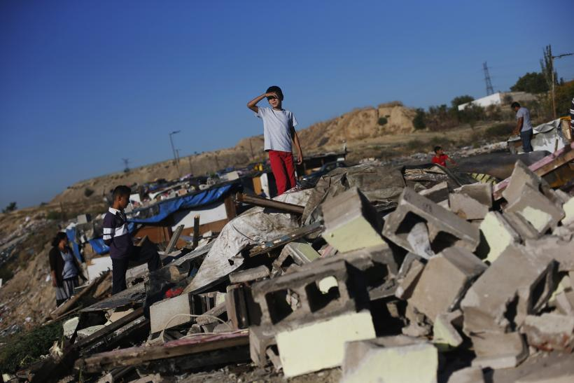 A child looks on at the remains of a home demolished by police during an operation in Madrid's
