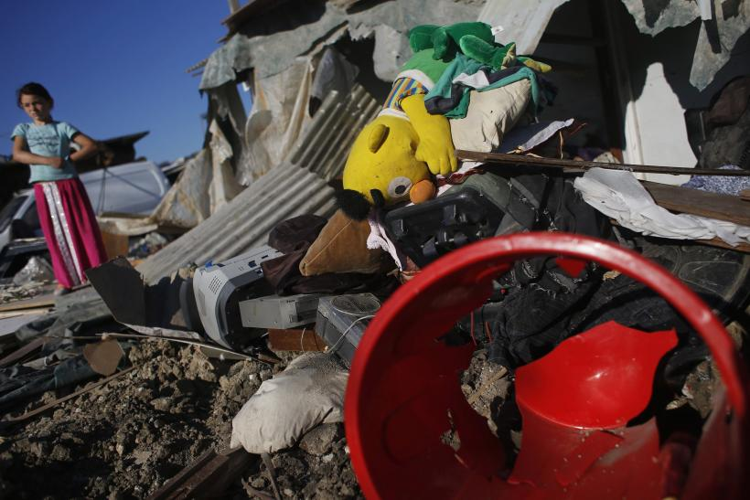 A girl stands next to the remains of home demolished by Spanish police during an operation in Madrid's 'El Gallinero' slum.