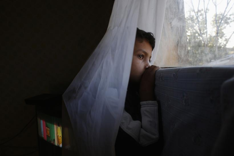 Six-year-old Abel watches from his window as an excavator demolishes a neighbor's shack in Madrid's