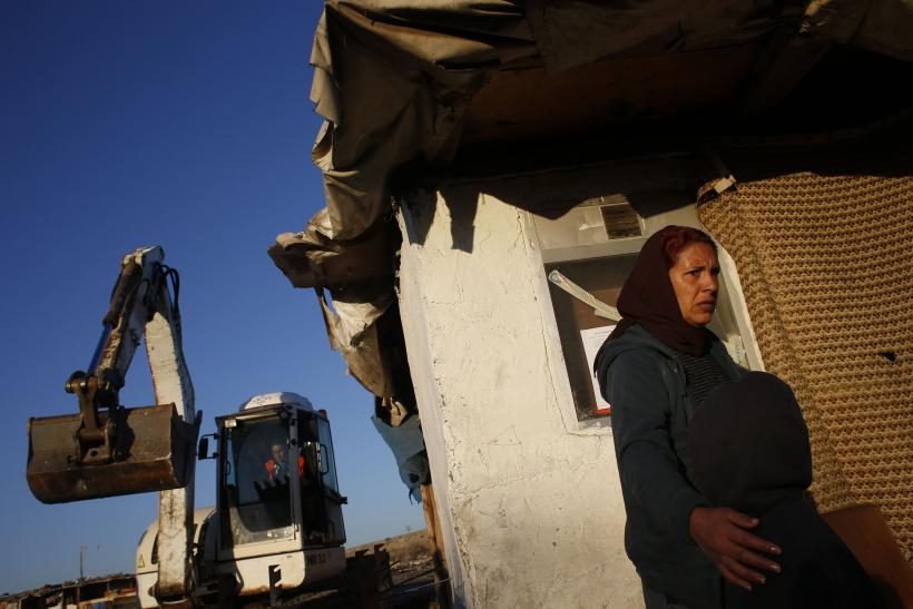 A woman moves her son away from the path of a bulldozer, as Spanish police proceeded to demolish several homes in her neighborhood, Madrid's notorious