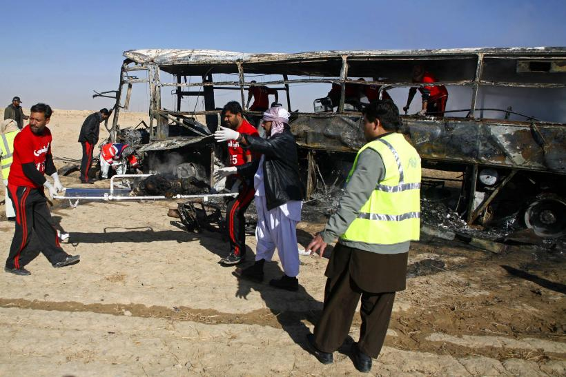 Emergency personnel remove burnt human remains from the scene on a stretcher, after a car bomb exploded in Quetta