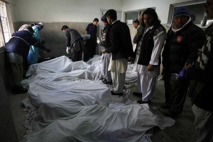 Paramedics inspect the bodies of Shia Muslim pilgrims killed by a car bomb in Quetta