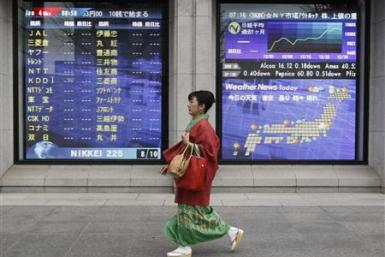 Woman in kimono walks past a stock quotation board outside a brokerage in Tokyo