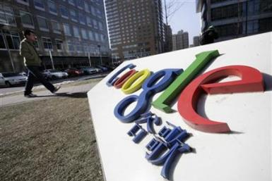 A man walks past a logo of Google China in front of its headquarters in Beijing