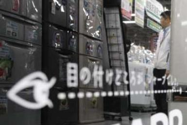 A man is reflected on Sharp's logo on its fridge at an electronic shop in Tokyo October 29, 2009.