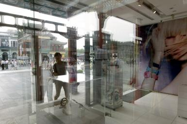 Customers walk into a Swatch shop along the Qianmen shopping street in Beijing