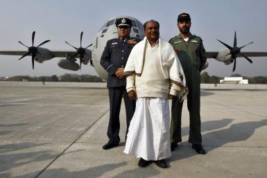 India's Defence Minister Antony, India's Air Chief Marshal Naik and Singh, an Air Force official, pose in front of the Super Hercules aircraft at Hindan