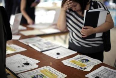 A woman browses job openings at a job fair in Los Angeles