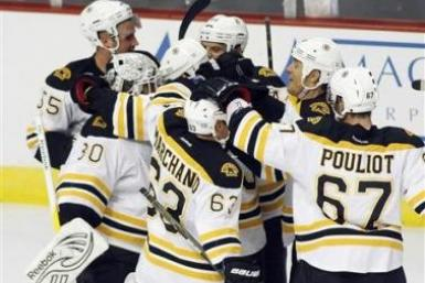 Boston Bruins players congratulate goalie Tim Thomas (L) after defeating the Chicago Blackhawks 3-2 in a shootout during their NHL hockey game in Chicago