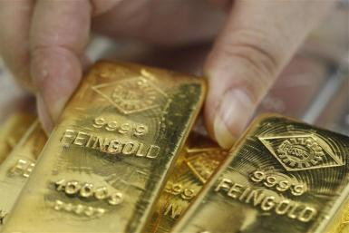 An employee picks up a gold bar at the Austrian Gold and Silver Separating Plant 'Oegussa' in Vienna