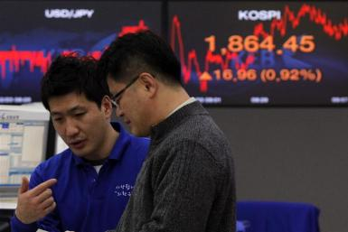 Foreign currency dealers from the Korea Exchange Bank are seen in front of a monitor displaying the current Korea Composite Stock Price Index (KOSPI) at the KEB in Seoul