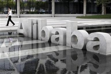 A man walks past a logo of Alibaba (China) Technology Co. Ltd at its headquarters on the outskirts of Hangzhou, Zhejiang province