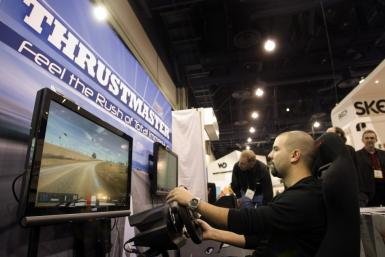 Corrado Amenta, tries out a driving simulation game with Thrustmaster steering wheels and pedals by Guillemot Corp. during the 2011 International Consumer Electronics Show (CES) in Las Vegas