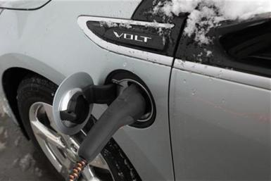 A 2012 Chevrolet Electric Volt gets charged at a charging station at a Chevrolet car sales lot in Troy, Michigan