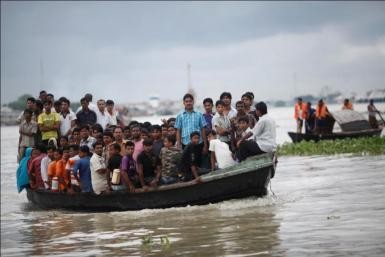 An overcrowded ferry crosses the River Shitalakkhya, while a rescue team is seen on right after another ferry was struck by a sand barge and capsized in Narayanganj.