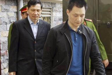 Pham Thanh Binh, former chairman of shipbuilding group Vinashin, and Nguyen Tuan Duong are escorted by policemen to a court in Hai Phong