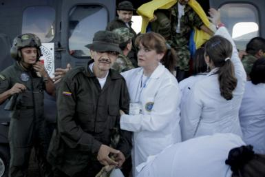 A Colombian policeman recently freed by FARC rebels is helped by a medical personnel after arriving at Villavicencio airport