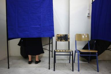 Woman stands in voting booth at an Athens polling station during Greece's national election