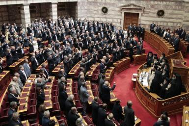 Newly appointed lawmakers raise their arms during a swearing in ceremony in Athens