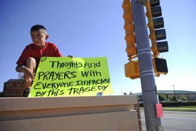 Brendon Hutchinson, 11, of Aurora, Colorado sits at the intersection north of the Century 16 theater shootings in Aurora,