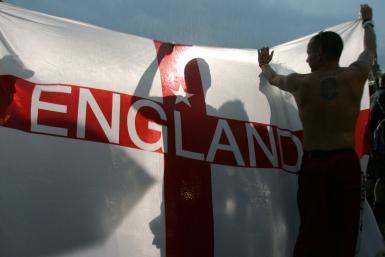 A England soccer fan celebrates with a St. George cross flag