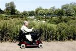 An elderly man in a electric wheelchair smokes a cigar as he rides through Hyde Park in London, May 19, 2010.