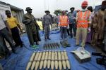 Security officials stand around illegal ammunition at Nigeria's main seaport in Lagos