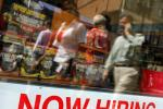"Pedestrians walk past a ""Now Hiring"" sign in the window of a GNC shop in Boston, Massachusetts September 1, 2010."