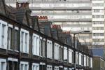 A terraced row of houses is pictured in front of a residential tower block in London