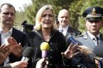 Marine Le Pen gestures as she talks with reporters before visiting the immigration centre at the Italian Island of Lampedusa
