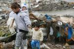 Family walks past rubble after the earthquake and tsunami in Minamisanriku City