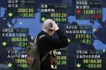 A man looks at the closing price of Japan's Nikkei share average displayed along with major indices outside a brokerage in Tokyo