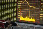 A man sits in front of an electronic board showing stock information at a brokerage house in Huaibei