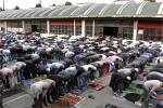 Muslims celebrate Friday prayers outside in the courtyard of a former fire brigade in Paris
