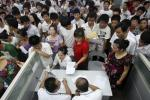 Jobseekers pass their resumes to representatives from Foxconn at a job fair in Zhengzhou