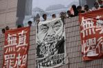 Artists hold banners including one featuring a portrait of detained Chinese artist Ai Weiwei during a protest in Hong Kong.