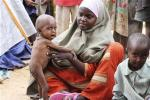 An internally displaced woman sits with her malnourished children