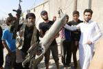 ISIS militants hold pieces of a Syrian jet near to Raqqa.
