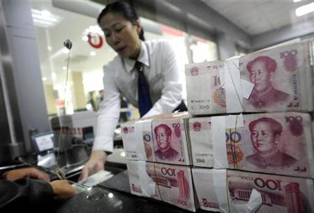 An employee hands Renminbi banknotes to a customer at a branch of the Industry and Commercial Bank of China in Hefei