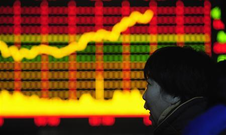 A woman looks at an electronic board with stocks information at a brokerage house in Hefei