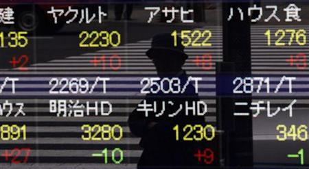 A pedestrian is reflected in a stock index board outside a brokerage house in Tokyo