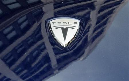 A logo of Tesla Motors on an electric car model is seen outside a showroom in New York