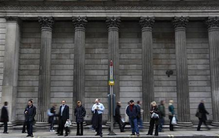 People wait at a bus stop outside the Bank of England in central London