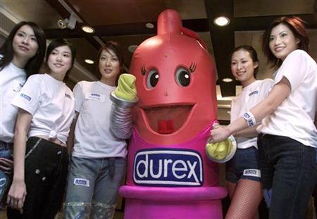 Models pose with a replica of a condom during the 2001 Durex Global Sex Survey Press conference in Hong Kong